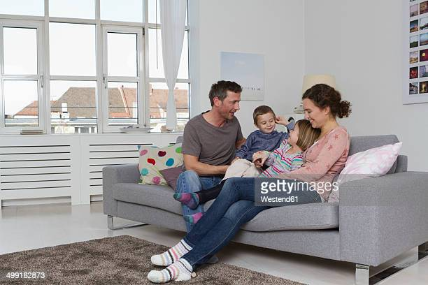 Happy family of four sitting on couch