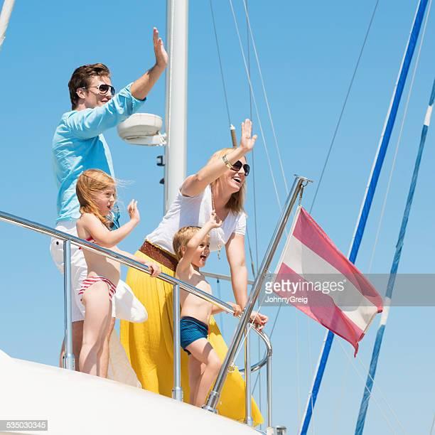 Glückliche Familie von vier winkt vom Yacht gegen blauen Himmel
