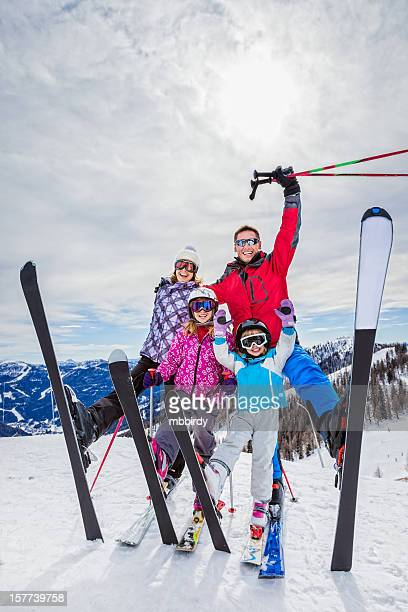Happy family of skiers on top (of ski resort)