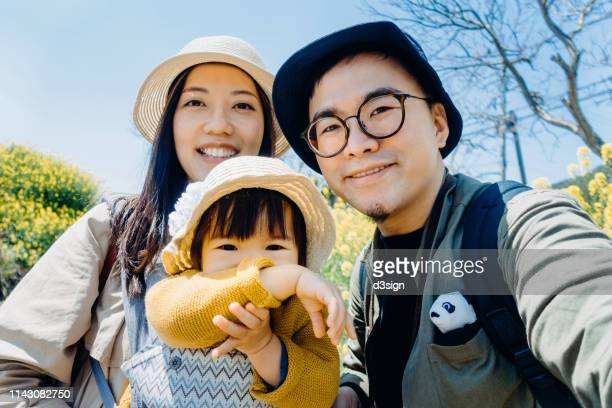 happy family of three having fun and enjoying family time in oilseed rape field on a lovely sunny day - self portrait photography stock pictures, royalty-free photos & images