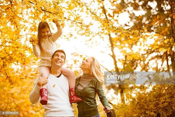Happy family of three in autumn park