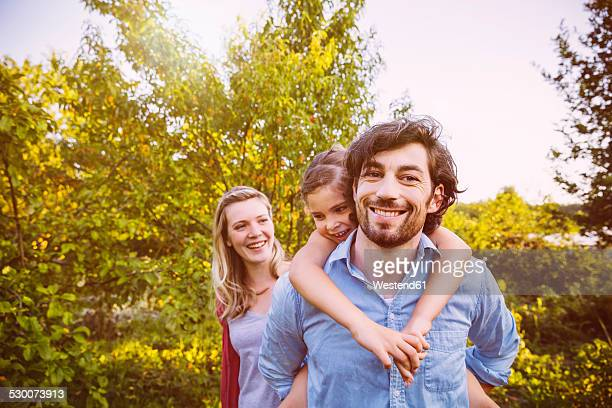 Happy family of three in garden at sunset