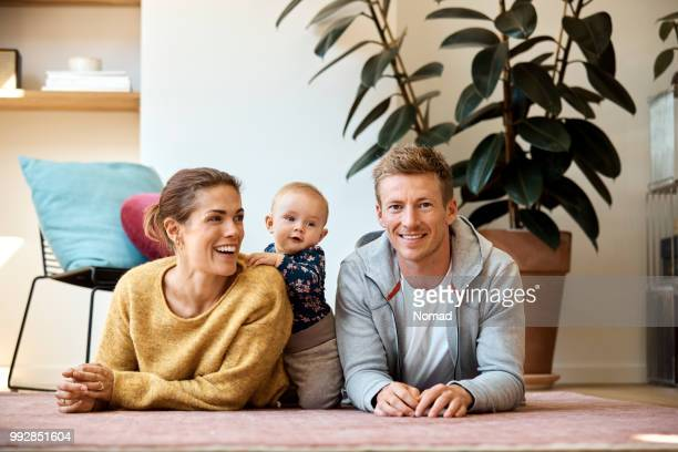 happy family of three lying on carpet at home - nordic countries stock photos and pictures