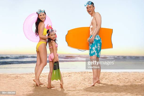 a happy family of three playing on the beach - chinese bikini girls stock pictures, royalty-free photos & images