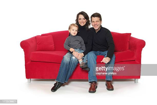Happy Family of Three Sitting on a Big Red Couch