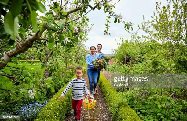 Happy family of three walking through their farm