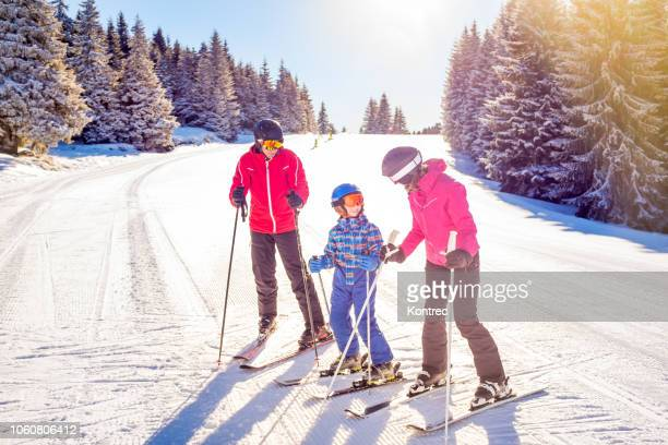 happy family on a ski trip - ski holiday stock photos and pictures