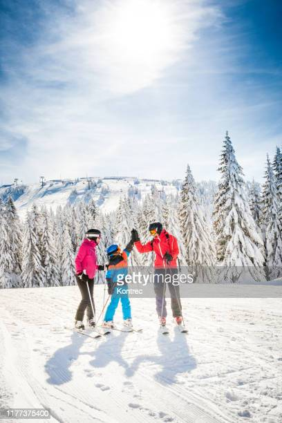 happy family on a ski trip - skiing stock pictures, royalty-free photos & images