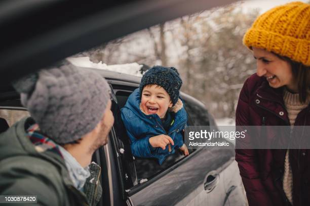 happy family on a winter road trip - winter family stock photos and pictures