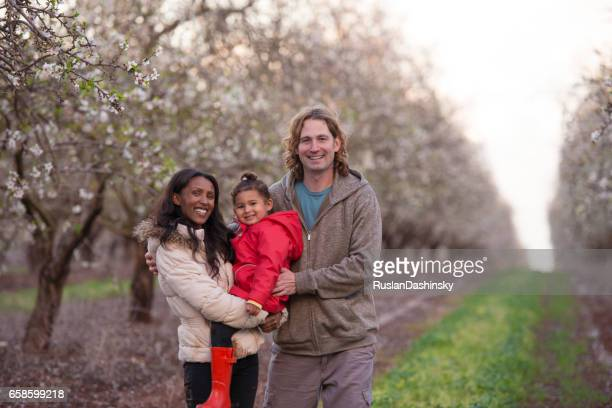Happy family on almond field in springtime.