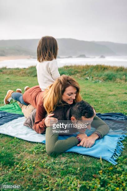 Happy family on blanket at the coast