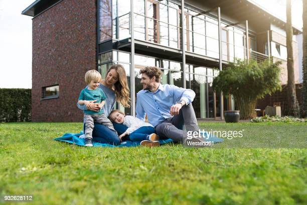 Happy family on blanket in garden in front of their home