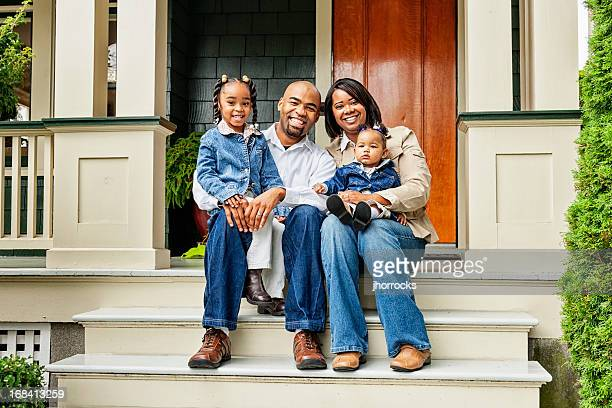 happy family on front porch - african american family home stock photos and pictures