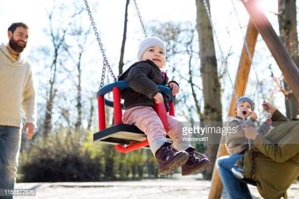 happy family on playground - kinderspielplatz stock-fotos und bilder