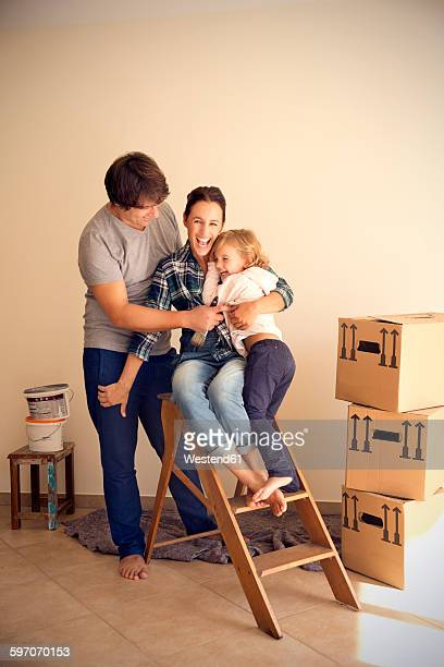 Happy family on step ladder beside cardboard boxes