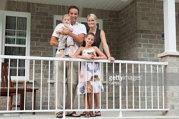 Glückliche Familie auf dem Balkon Ihres neuen Hauses
