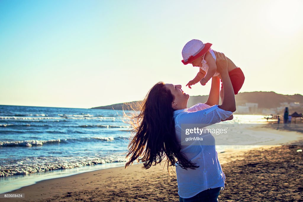 Happy family on the beach. mother hugging her baby girl : Stock Photo