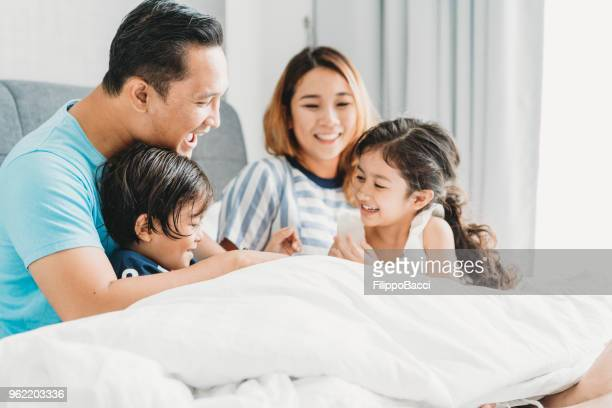 happy family on the bed together - malaysian culture stock pictures, royalty-free photos & images