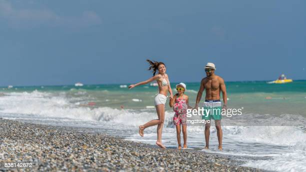 Happy family on the tourist resort hotel beach