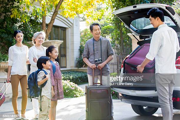 Happy family packing for car trip