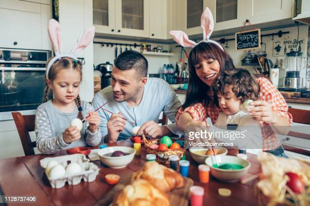 happy family painting easter eggs - pasqua foto e immagini stock