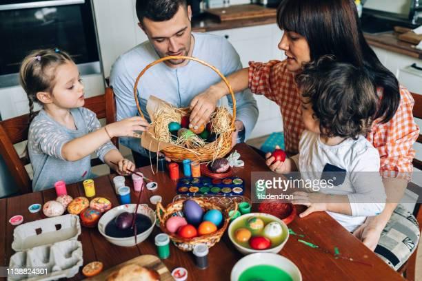 fröhliche familienmalerei ostereier - osternest stock-fotos und bilder