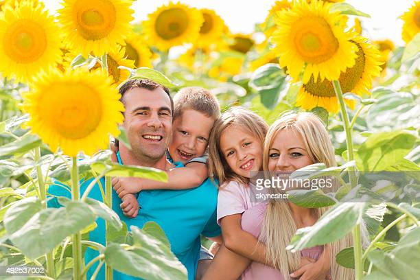 Happy family piggybacking among sunflowers and looking at camera.