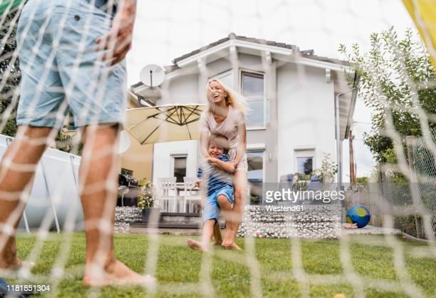 happy family playing football in garden - mama futbol fotografías e imágenes de stock