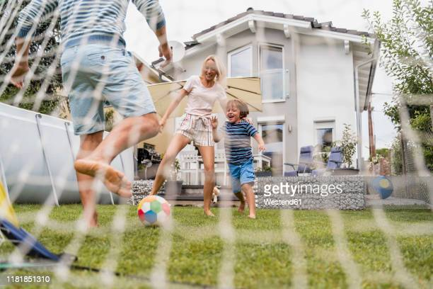 happy family playing football in garden - sporting term stock pictures, royalty-free photos & images