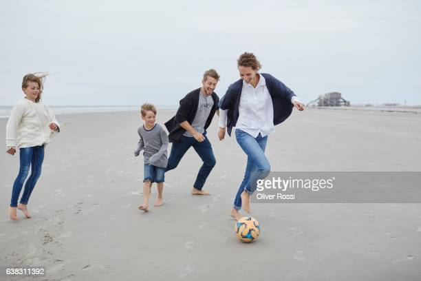Happy family playing football on the beach