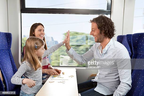 Happy family playing in a train