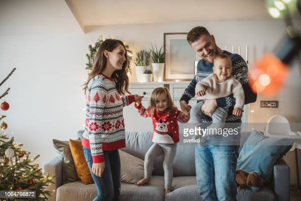 happy family playing in living room - christmas jumper stock photos and pictures