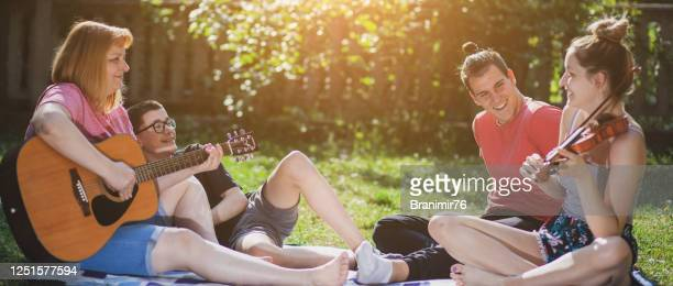 happy family playing music and enjoying in nature - stringed instrument stock pictures, royalty-free photos & images