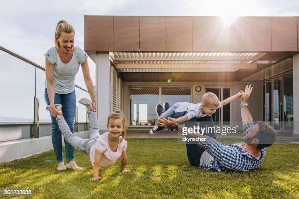 Glückliche Familie spielen auf dem Rasen vor ihrem Penthouse.