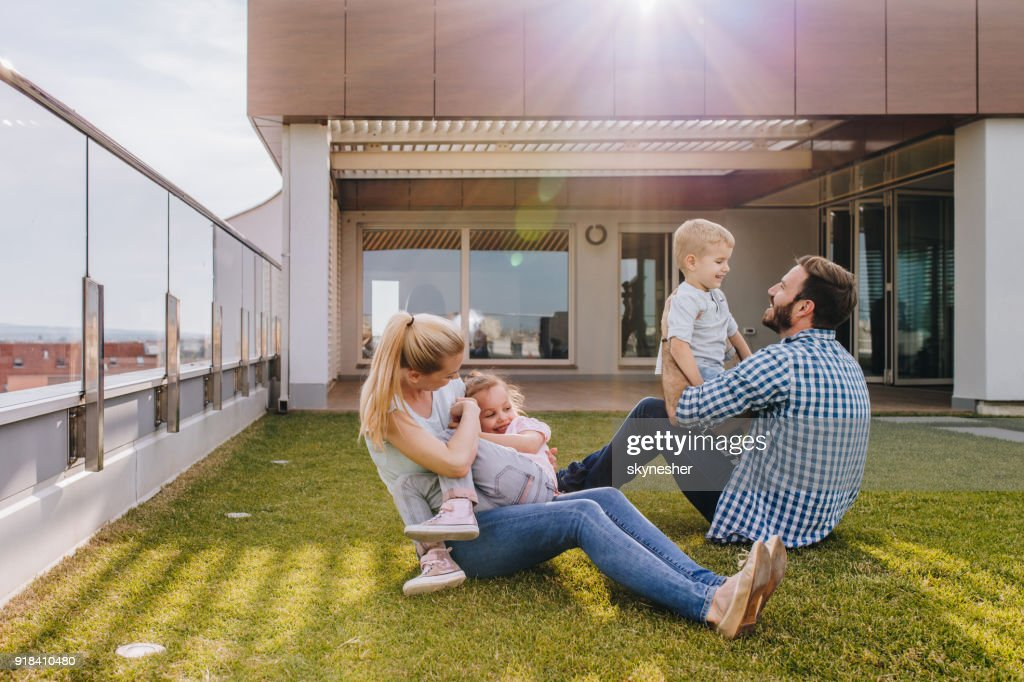 Happy family playing on the grass in front of their penthouse. : Stock Photo