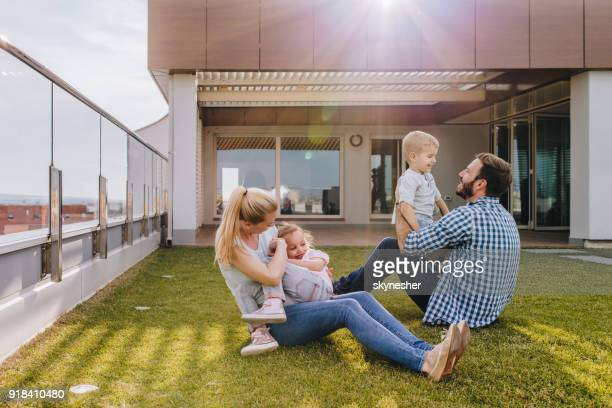 happy family playing on the grass in front of their penthouse. - penthouse girls stock pictures, royalty-free photos & images