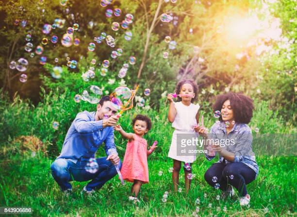 happy family playing soap bubbles in park. - black family fun stock photos and pictures