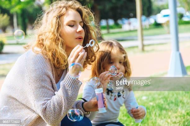 Glückliche Familie spielen Seifenblasen im park.