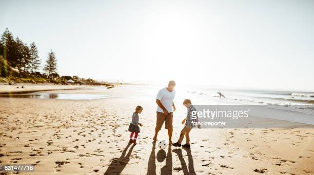 happy family playing soccer on the beach - queensland stock pictures, royalty-free photos & images