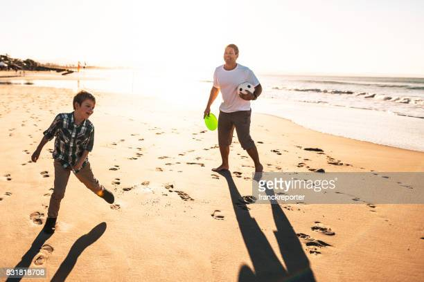 happy family playing soccer on the beach