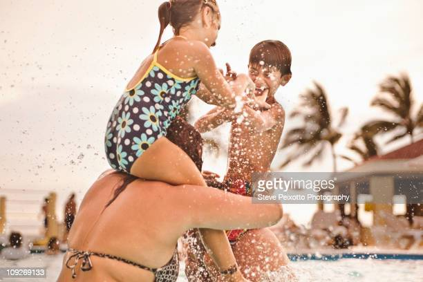 Happy family playing together in swimming pool