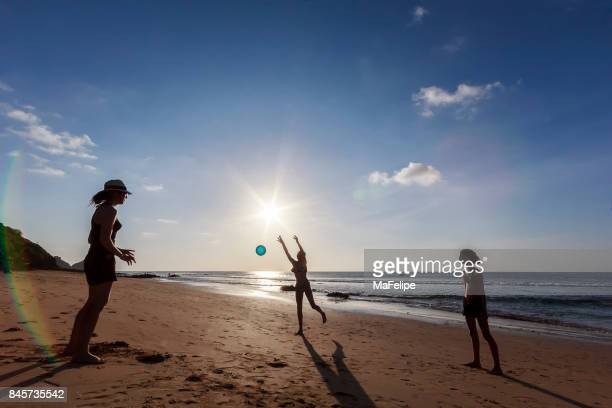 Happy family playing volleyball at the beach