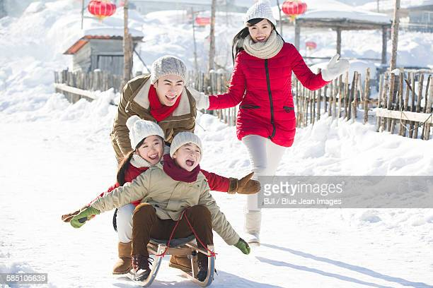 Happy family playing with sled in the snow
