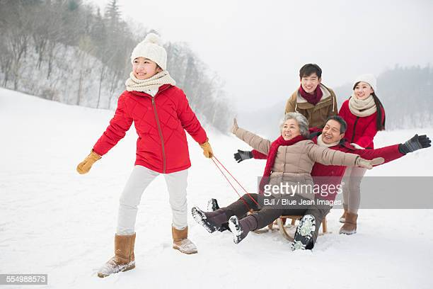 happy family playing with sled on the snow - harbin winter stock pictures, royalty-free photos & images