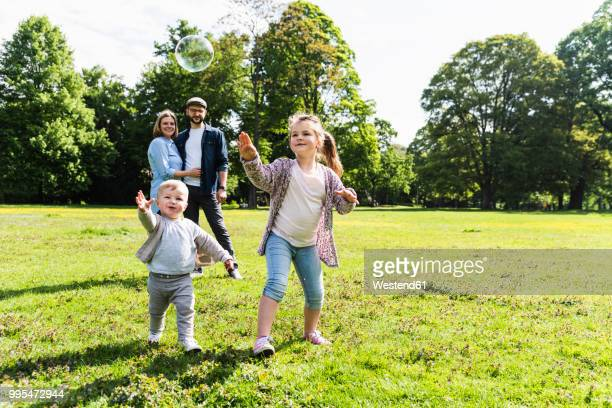 happy family playing with soap bubble in a park - junge familie stock-fotos und bilder