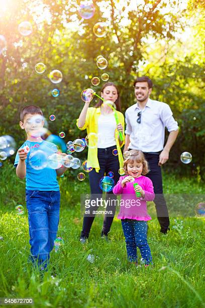 Happy family playing with Soap Bubbles