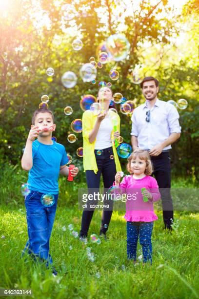 Glückliche Familie spielen mit Seifenblasen