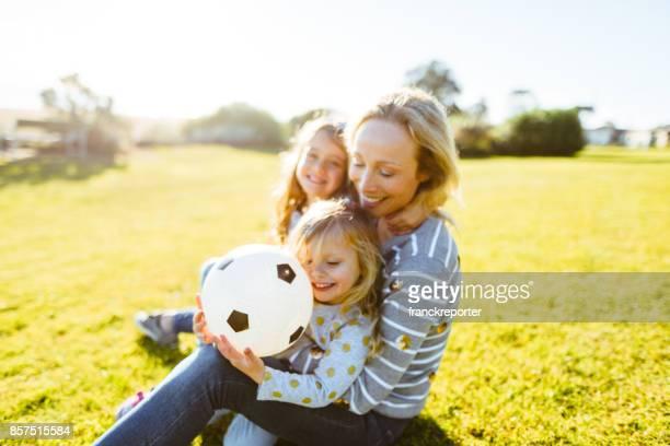 familia feliz jugando con balón de fútbol en el parque - mama futbol fotografías e imágenes de stock
