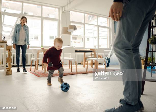 happy family playing with their son at home - spielball stock-fotos und bilder