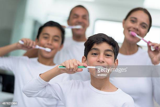 Happy family portrait brushing their teeth